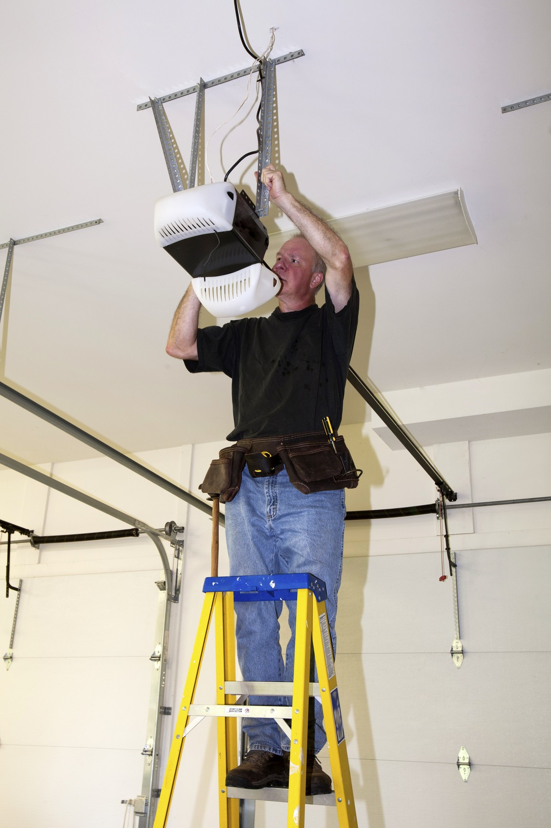 Man standing on a ladder fixing a mechanical garage door opener